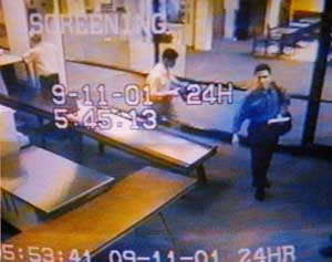 Abdulaziz Alomari, right, and Mohamed Atta, left (in dark shirt), passing through security in the Portland, Maine, airport. Note the different times on the two time stamps, one in the middle, one at the bottom.
