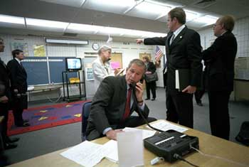 Bush in a holding room before giving his speech. Communications director Dan Bartlett points to the TV, and the clock reads 9:25.