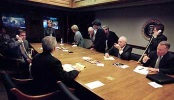 Vice President Cheney pointing a finger inside the Presidential Emergency Operations Center. Footage of the World Trade Center plays on the televisions in the background (exact time is unknown).