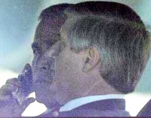 Bush trying to use a cell phone while sitting next to Andrew Card as his motorcade nears the Sarasota airport.