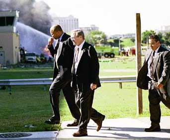 "This picture of Rumsfeld (center), taken from the US Army website, is captioned, ""Secretary of Defense Donald H. Rumsfeld returns to Pentagon inner offices Tuesday morning after surveying the damage from the hijacked plane which crashed into the building moments before."" This contradicts his claim that he was helping victims for nearly an hour after the attack. However, there is video footage of Rumsfeld helping a person on a stretcher and it is not known when this picture is taken exactly."