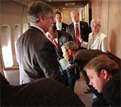 President Bush (center, bending) and others look out  the windows of Air Force One as their fighter escort arrives.