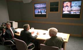President Bush takes part in a video teleconference at Offutt Air Force Base. Chief of Staff Andrew Card sits on his left, and Admiral Richard Mies sits on his left.