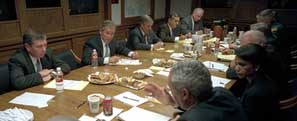"President Bush (below television screen) meeting with the National Security Council in a bunker below the White House. In the far row from left to right, are Attorney General Ashcroft, President Bush, Chief of Staff Card, CIA Director Tenet, and counterterrorism ""tsar"" Ckarke. In the near row, Secretary of State Powell can be seen waving his hand, and National Security Advisor Rice sits to his right."
