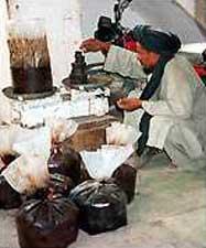 An Afghan refines opium into heroin.