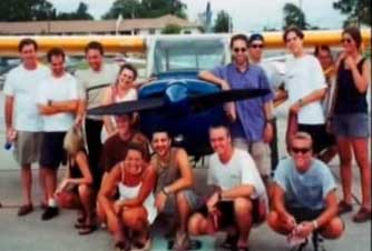 Ziad Jarrah, with dark blue shirt and sunglasses, leaning against an airplane. He is surrounded by his fellow flight school students.