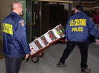 US Customs Agents carry out boxes of evidence from SAAR network businesses on March 20, 2002.