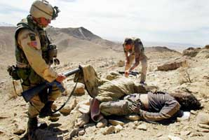 US troops investigate two dead bodies on March 17, 2002, as Operation Anaconda comes to a close.