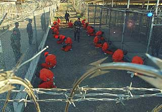 Camp X-Ray prisoners. Their detention cages can be seen on the right. Pictures like this provoked an outrage about their treatment.
