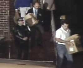 Invesigators remove boxes of evidence from El Sayyid Nosair's residence hours after the assassination.