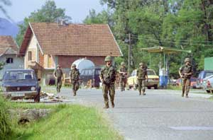 NATO troops patrol the village of Bocinja Donja in 2001.