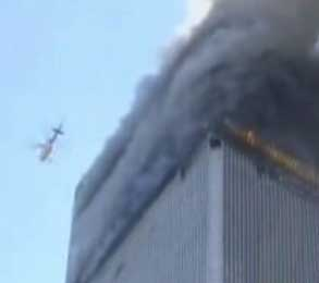 A helicopter flying above the burning World Trade Center.