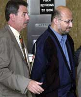 Sami al-Arian being led from a courthouse in handcuffs.