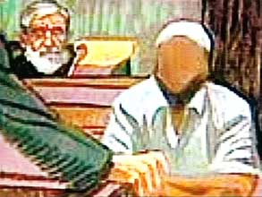 Jamal al-Fadl testifying in a courtroom. Because his identity has been kept secret, his face has been blocked out.