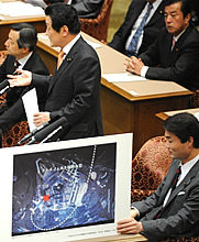 Yukihisa Fujita holding up a picture showing the trajectory of Flight 77 heading into the Pentagon.