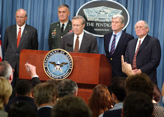 Donald Rumsfeld speaking at his 6:42 p.m. news briefing. Behind the secretary of defense, left to right, are Thomas White, Henry Shelton, John Warner, and Carl Levin.
