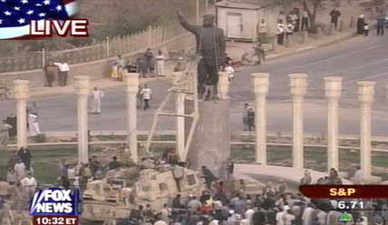A US military vehicle pulls down a statue of Saddam Hussein in front of a small crowd.