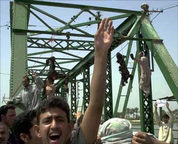 The burned, mutilated corpses of two Blackwater contractors hang from a bridge outside Fallujah while Iraqi civilians celebrate.