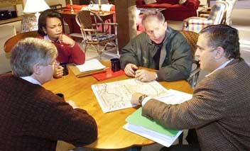 George Tenet pointing at a map and describing CIA operations in Afghanistan on September 30, 2001. Also at the table are George Bush, Condoleezza Rice, and Andrew Card.