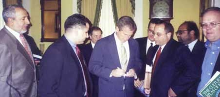 Abduraham Alamoudi (far left), Bush (center), and Rove (far right). Judging from the background, this picture was probably taken in 2000.