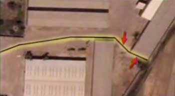 Satellite photo of the Djerf al Nadaf site, showing the wall blocking the truck route. Red arrows indicate where trucks were supposed to pass through the wall.