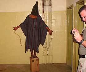The detainee nicknamed Gilligan stands on a box, fearing electrocution. Ivan Frederick stands at the side with a camera in his hands.