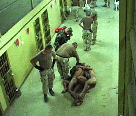 Three Abu Ghraib detainees naked and cuffed together.