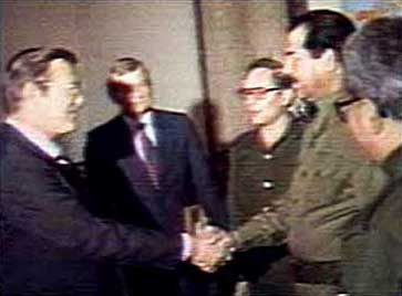Rumsfeld greets Hussein.