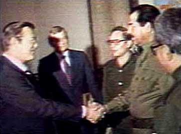 Rumsfeld greets Hussein.