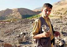 A Kurdish soldier allied with US forces stands on the site where the Sargat training camp used to be. He holds a piece of a US cruise missile that hit the camp.