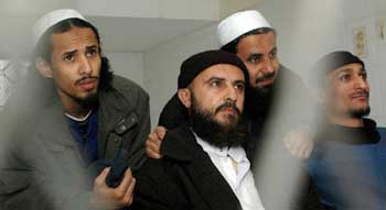 Fahad al-Quso, far left, Jamal al-Badawi, in center with black cap, and two other militants in a Yemeni prison in February 2005.