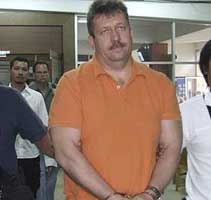 Victor Bout in handcuffs in Thailand on the day of his arrest.