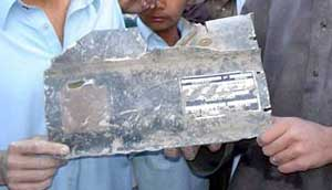 Pakistanis hold up a piece of the missile that allegedly killed Abu Hamza Rabia.