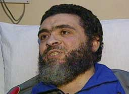 Ahmed Said Khadr in a hospital bed during his hunger strike, being visited by journalists.