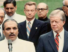 Front row: Pakistani President Muhammad Zia ul-Haq  (left) and President Carter (right). Zbigniew Brzezinski is in the center of the back row.