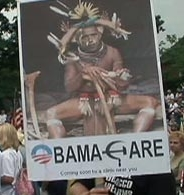 An anti-health care reform sign at the 9/12 rally depicting President Obama as a witch doctor, and combining the Obama 2008 campaign logo with the Soviet hammer and sickle.