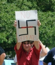 Anti-health care reform protesters displays sign with swastika prominently featured.