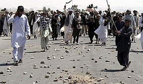 Angry Afghani citizens march in protest against the US air strike at Azizabad.