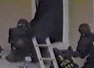 BATF agents attempt to force entry through a second-floor window of the Branch Davidian compound. At least one of the agents depicited will be shot in the firefight.