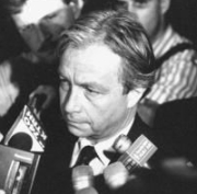 FBI agent Bob Ricks, surrounded by reporters during a press conference.