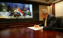 President Bush signs the &#8216;Declaration of Principles&#8217; as part of a teleconference with Prime Minister al-Maliki.
