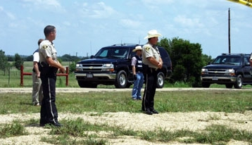 The Bush motorcade drives past Camp Casey; Texas police officers stand between the motorcade and the camp.
