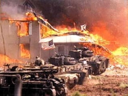 Combat engineering vehicles (CEVs) lined up outside the blazing Branch Davidian compound.
