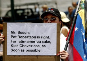A protester holds a sign signifying his agreement with Pat Robertson&#8217;s call to assassinate Venezuela&#8217;s Hugo Chavez.