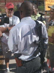Militia member Chris Broughton stands in front of a Phoenix VFW where President Obama is speaking. Broughton wears a pistol on his hip and an assault rifle strapped to his back.