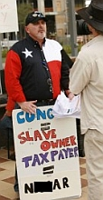 Dale Robertson, the leader of TeaParty.org, displays a handmade sign with a racial slur. Mediaite, the source of this photo, later blocked out a portion of the offending word. Robertson's sign itself is not blocked out.