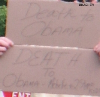 "A protester displays a handmade sign advocating ""Death to Obama"" and to his family."