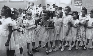 One of the first schools to implement desegregation is Barnard Elementary in Washington, DC. This photo shows black and white children in the same classroom.