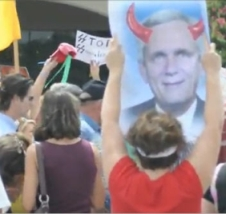 Anti-reform protesters carry signs depicting Doggett with 'devil horns' and a sign featuring Nazi SS lettering.