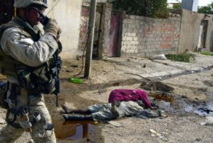 A Marine walks past several corpses strewn in a Fallujah street.